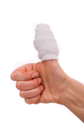 White medicine bandage on human injury hand finger. Studio isola